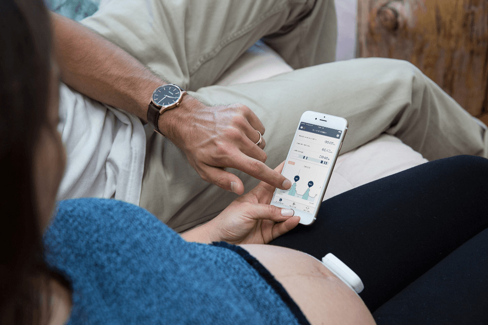image of woman and partner using Bloomlife smart pregnancy tracker to monitor contractions and labor in third trimester